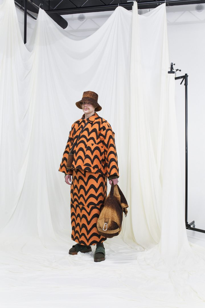 Model wearing a born & orange jacquard jacket with matching skirt, brown rug sack and a matching bucket hat.