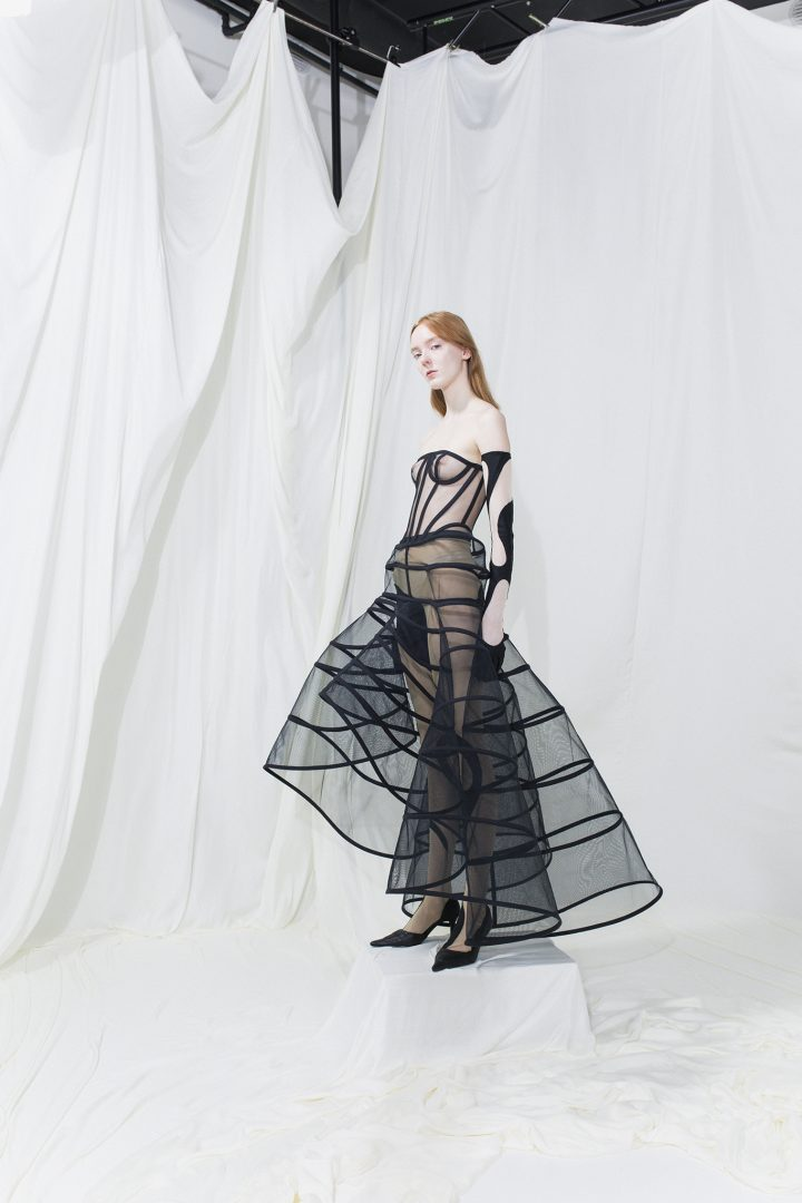 Model is wearing a black mesh fitted dress with see-through crinoline skirt. Black cut-out gloves and leggings.