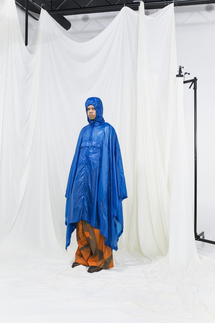 Model wearing a hood blue nylon raincoat with orange printed trousers underneath.