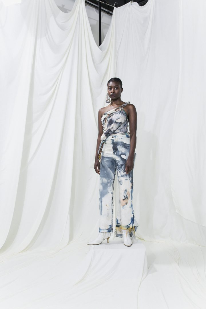 Model is wearing a black and white printed asymmetric sleeveless top and matching long trousers