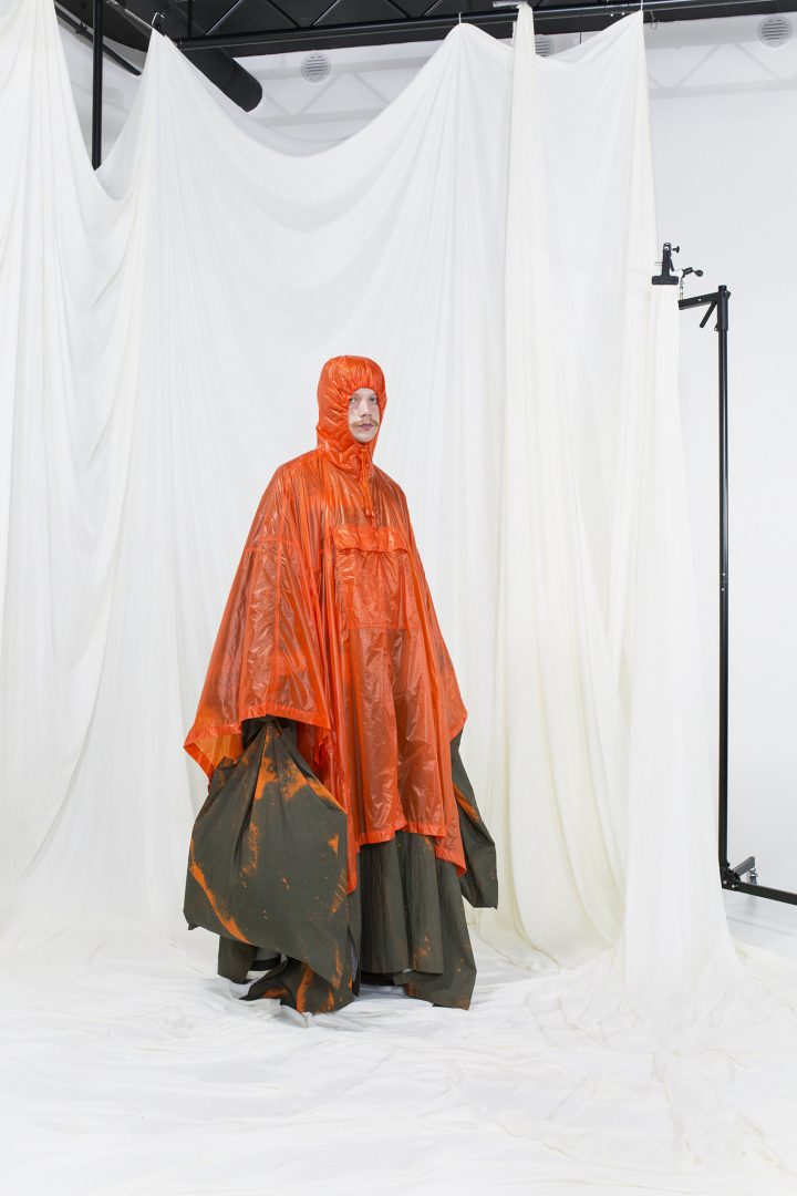 Model wearing a hooded orange nylon raincoat with green printed undercoat and bag