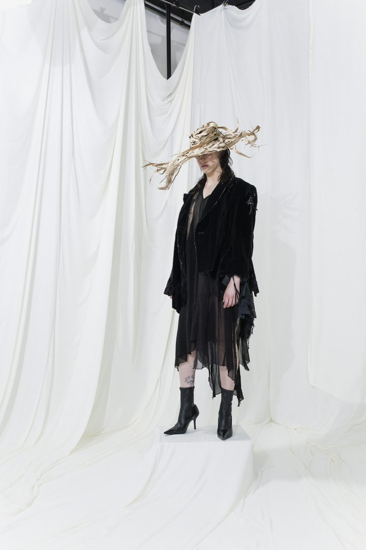 Model is wearing a black jacket and sheer asymmetric black skirt with a distorted hat