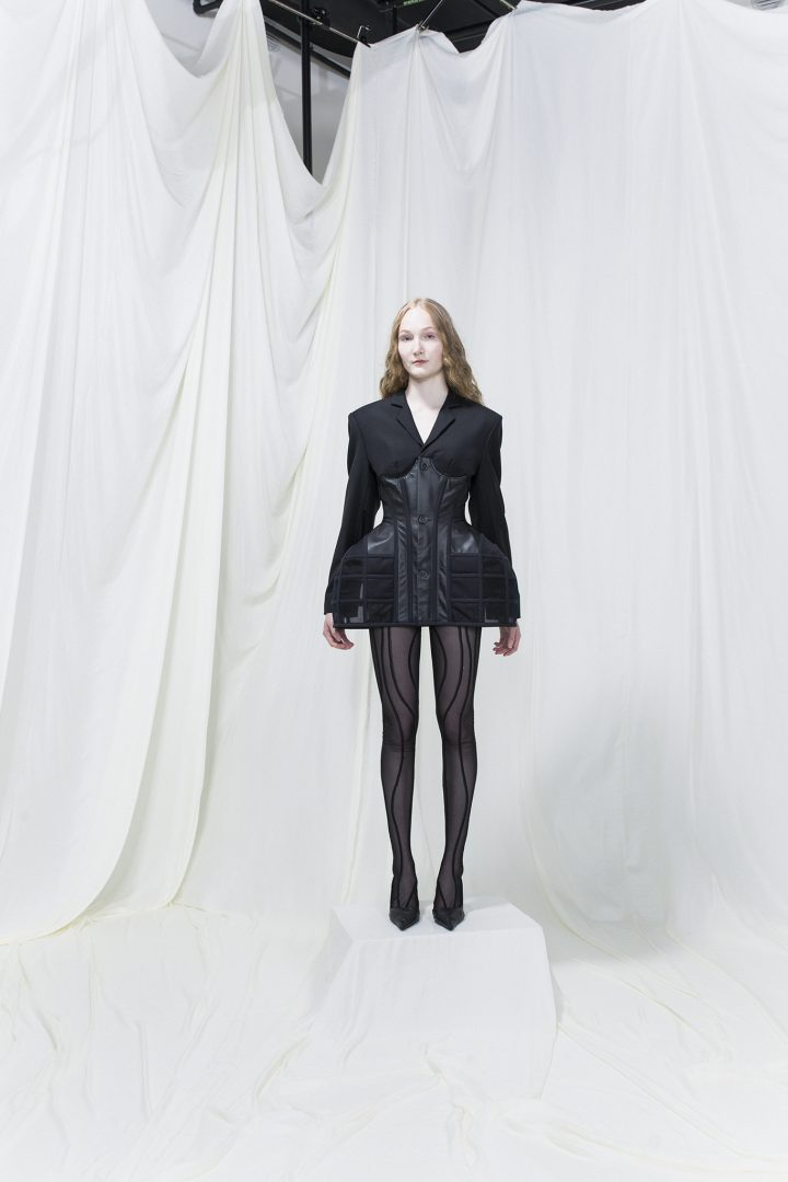Model wearing a black blazer with fitted leather corset with hip bustles on top. Black mesh stockings with stripes underneath