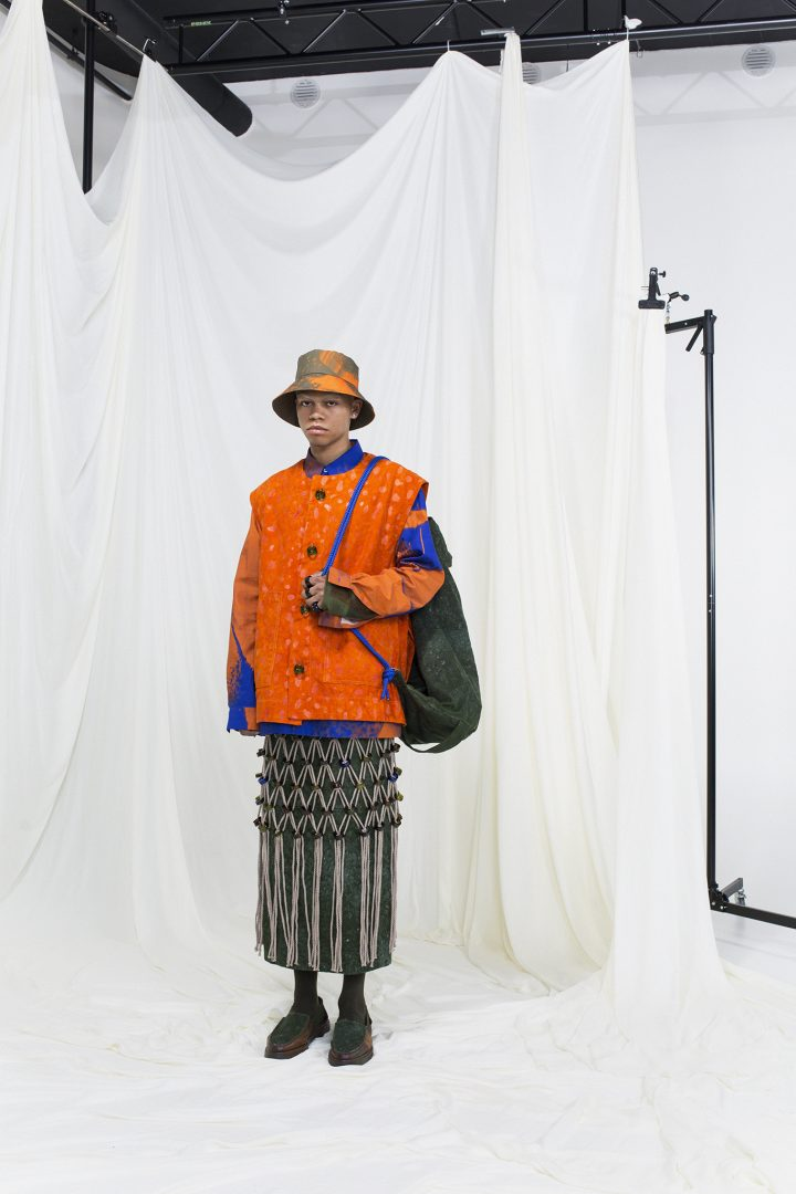 Model wearing a orange coat, geen skirt with macrame overskirt, green rug sack and a bucket hat