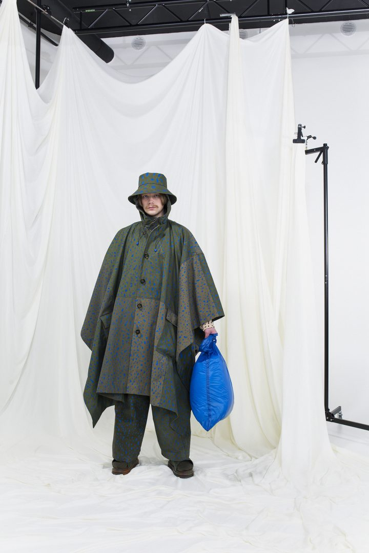 Model wearing a green hooded raincoat with blue dotted print, matching trousers, blue nylon bag and a bucket hat