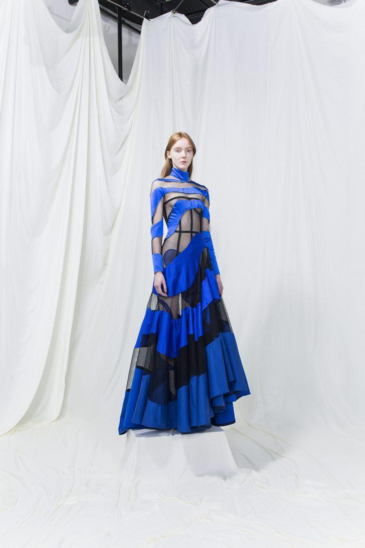 Model wearing a long blue dress with black mesh cutouts.