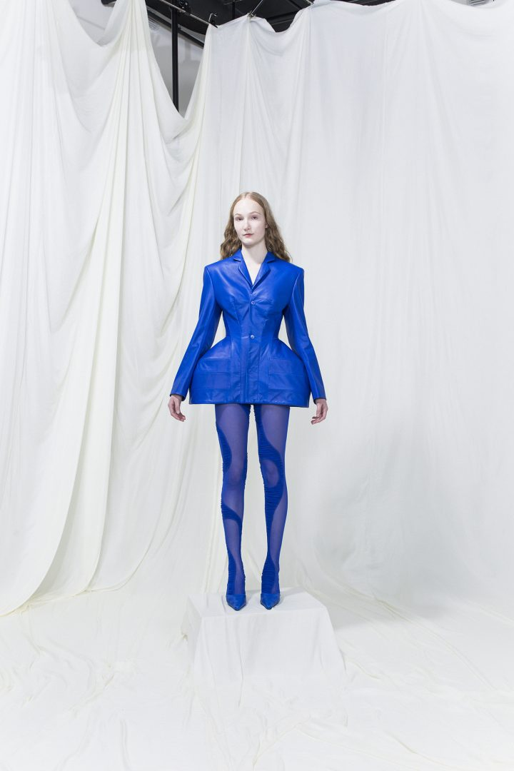 model wearing a fitted blue leather blazer with hip bustles, blue mesh leggings underneath