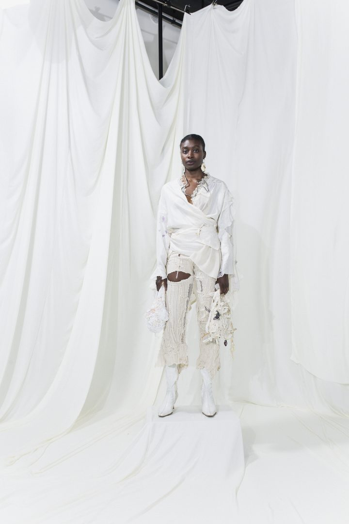 Model is wearing a white wrap shirt andoff-white striped trousers. On both hands they carry white bags