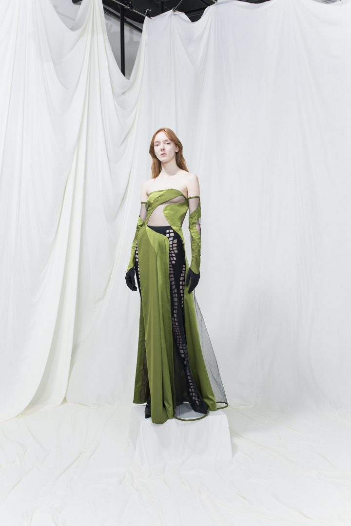 Model wearing a green long dress with cut-outs, cut-out leggings underneath