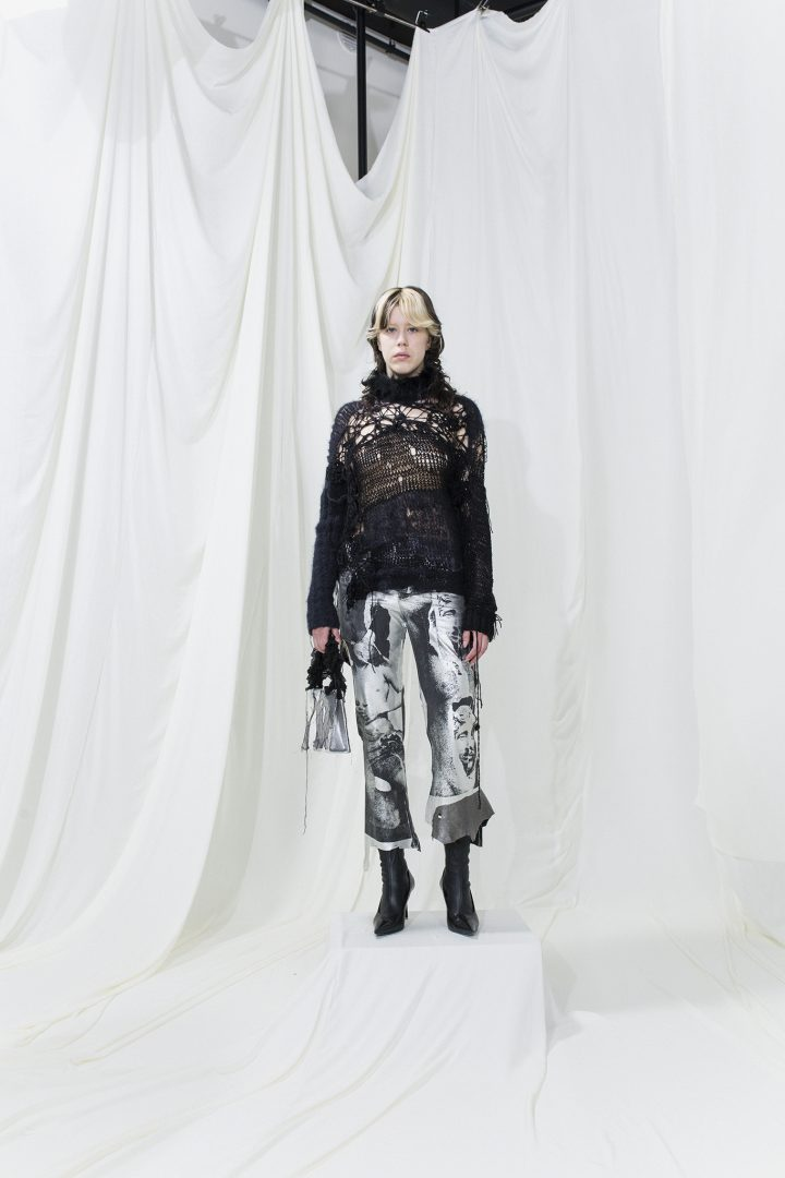 Model is wearing a black knit with holes in them and trousers with silver-grey print
