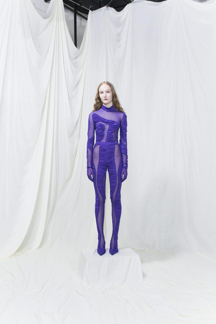 Model wearing a purple bodysuit with purple mesh cutouts.