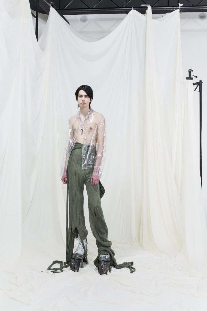 Model wearing long knitted and draped trousers and see through jacket
