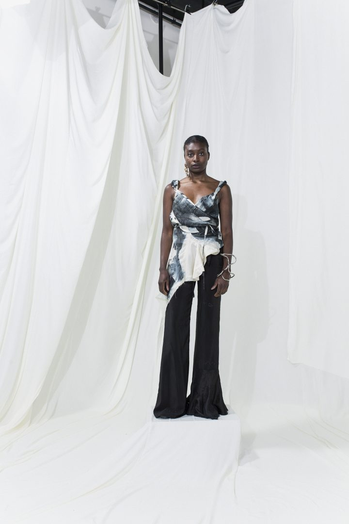 Model is wearing a blue and white printed top with long black trousers