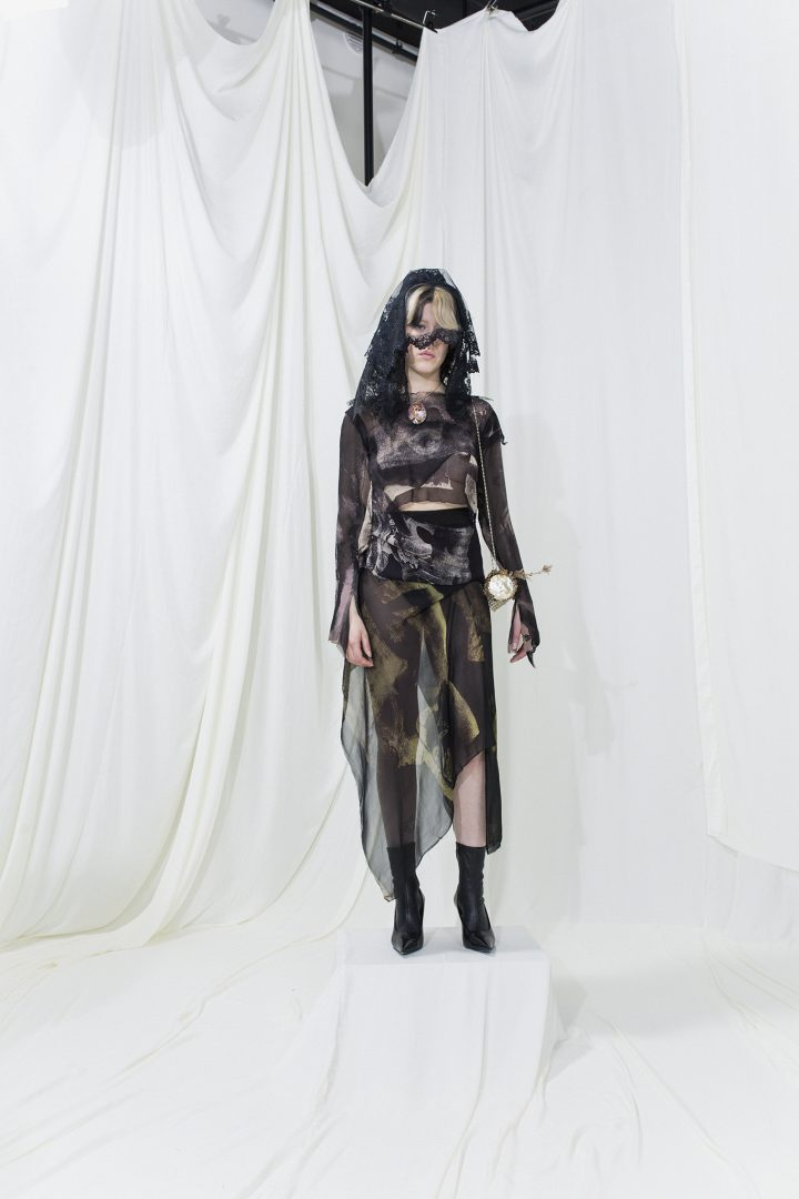 Model is wearing a black lace veil, printed top and asymmetric sheer skirt