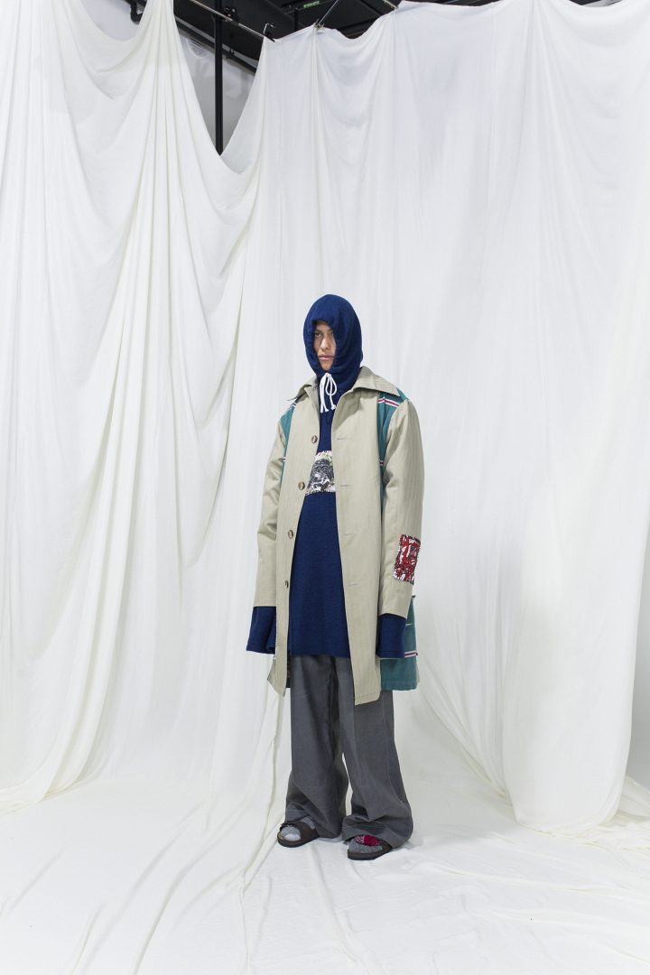 Model is wearing a panelled beige-green coat. Underneath navy blue long hoodie and grey oversized trousers