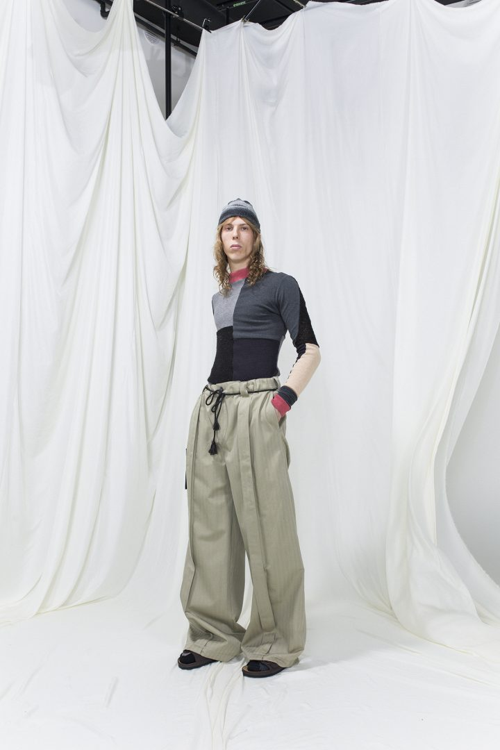 Model is wearing a panelled knitted top with red trimmings, oversized green-beige trousers and grey knitted hat