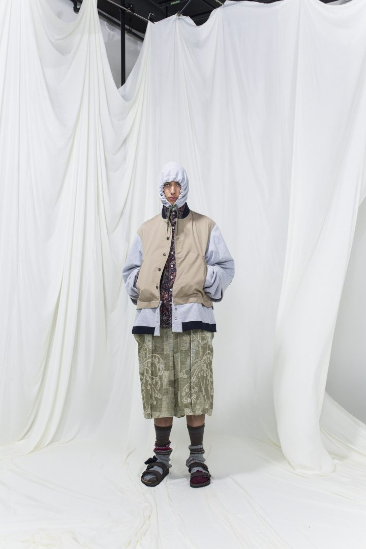 Model is wearing a panelled lilac and beige jacket with hoodie. Underneath green printed trousers and purple printed shirts. High socks and sandals as accessories