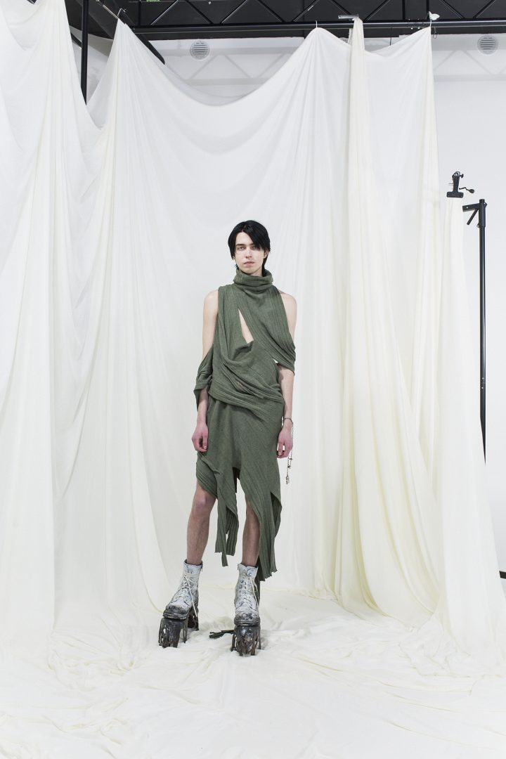 Model wearing sage green draped knitted dress with white boots