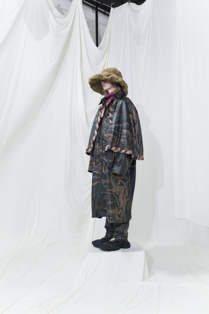 Long marble printed coat with extra cape worn with long marble-printed trousers. Brushed fur hat