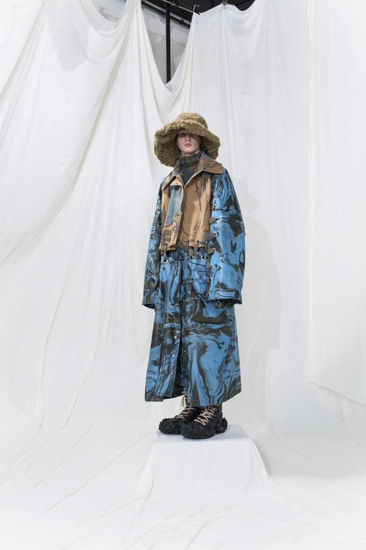 Marble printed machintosh coat in light blue and beige panels, connected with eyelets. Brushed fur hat