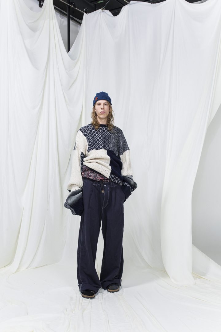 Model is wearing a panelled knitted jumper, oversized dark blue denim jeans and blue knitted hat