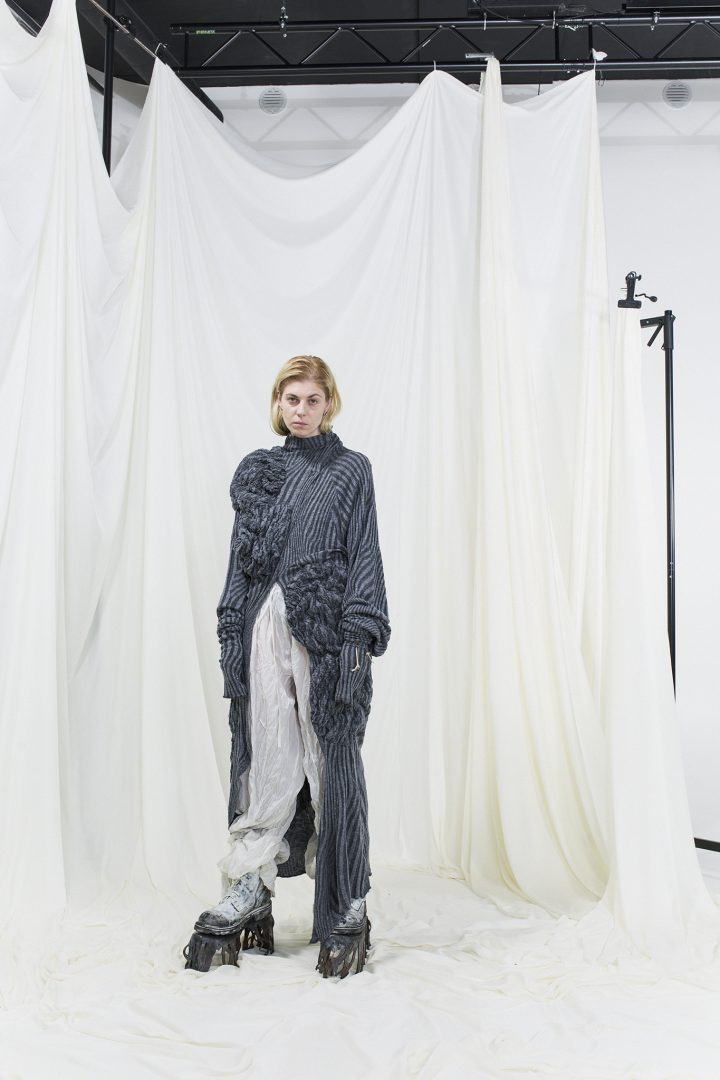 Model wearing silver and grey knitted long shirt and white crumpled trousers