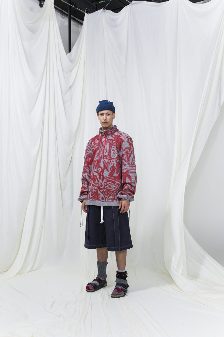 Model is wearing a printed red and grey jumper with denim shorts. Socks with sandals and blue knitted hat as accessories