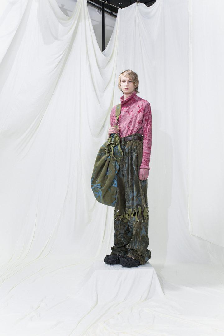 Pink marble printed turtleneck sweater with long dark green marble printed corduroy trousers. Large rucksack bag.