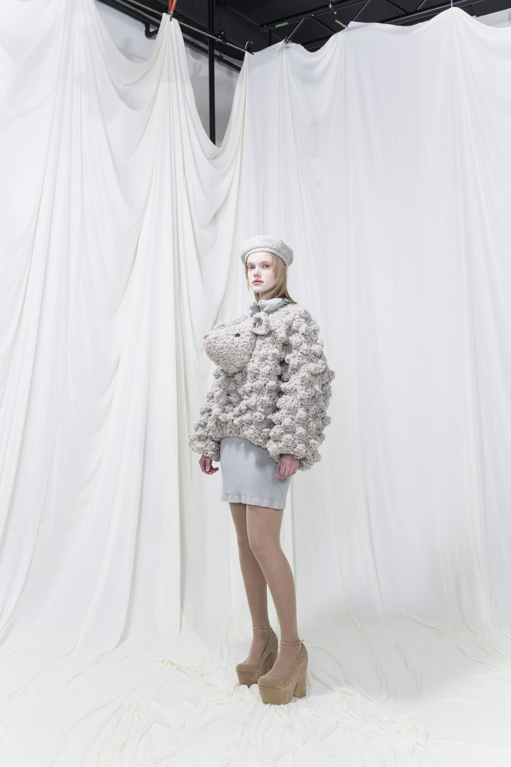 Knitted jumper resembling a sheep with glass eyes and embroidered nose. Grey pique dress underneath. Grey beret.