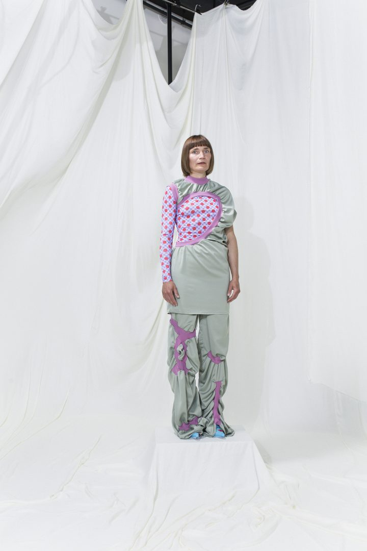 Model is wearing an asymmetrical gathered dress with hole with printed top and gathered trousers underneath