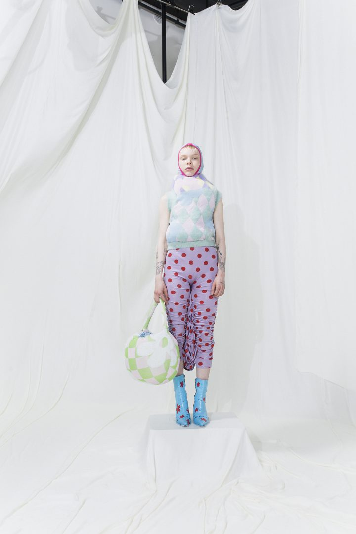 Model is wearing a knitted mohair puffy vest, floral scarf and pink printed trousers