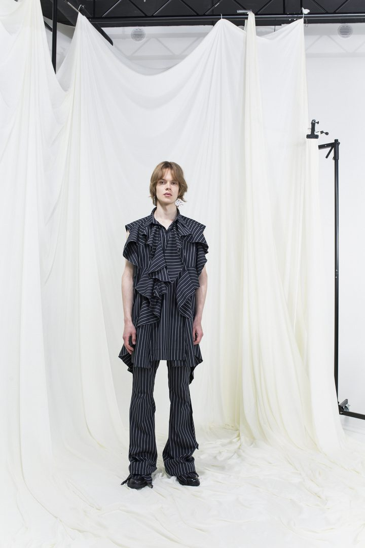 Model wearing a ruffled dark-blue and white pinstripe top and pinstripe bell-bottomed trousers