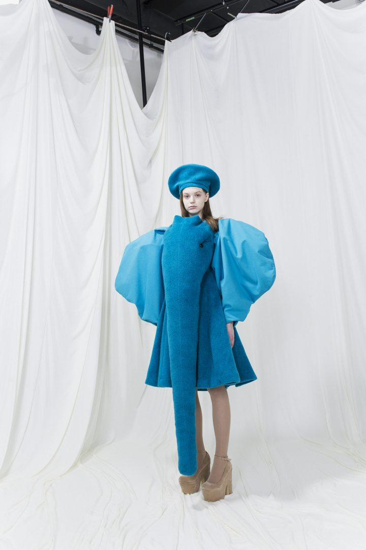 Blue dress resembling an elephant, balloon sleeves and trunk in the front. Blue beret.