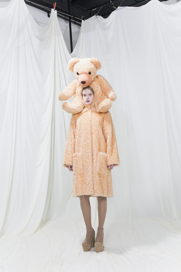 Model wearing a brushed fur coat with a teddy bear as a hood.