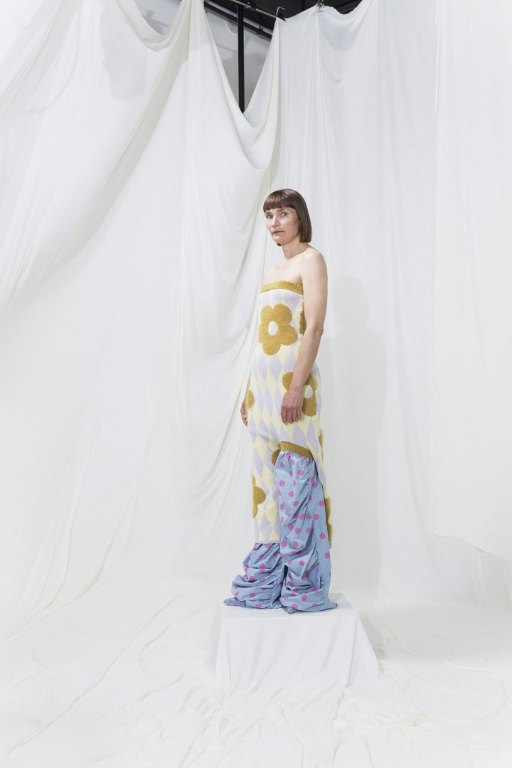Model is wearing an asymmetrical knitted floral mohair dress with draped printed lilac trousers