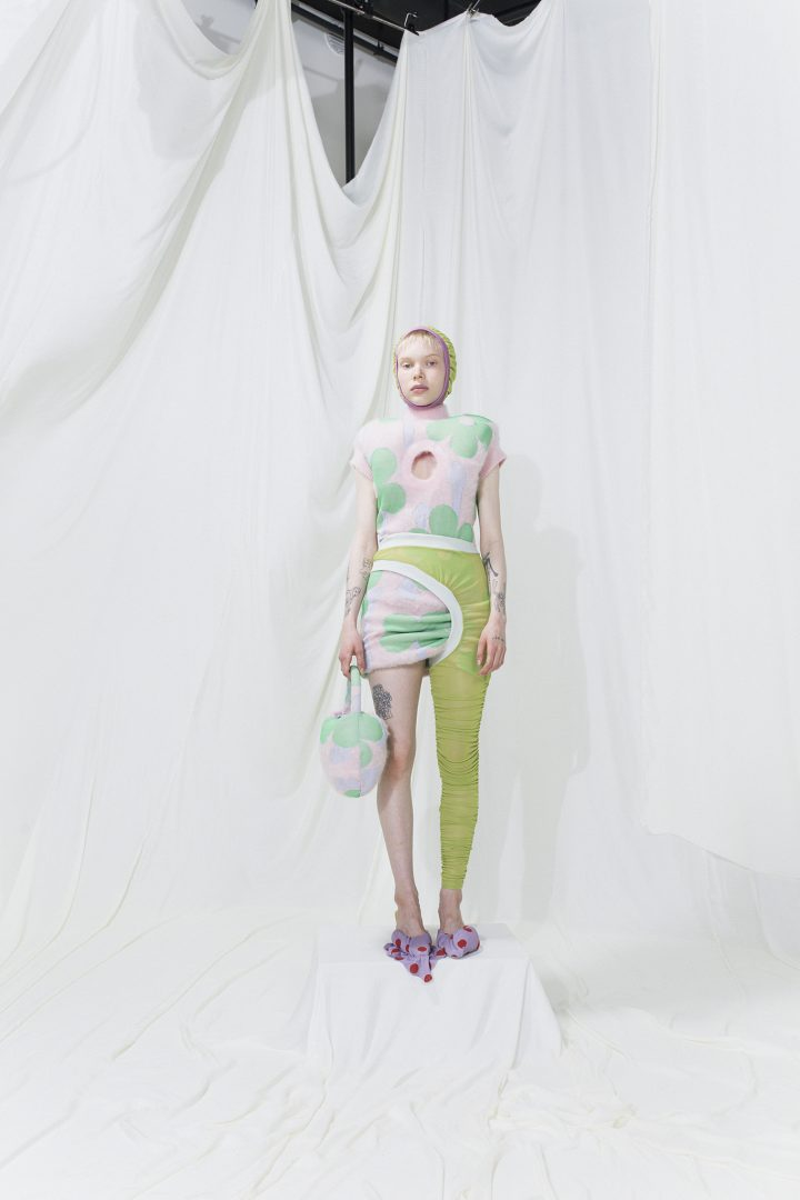 Model is wearing a knitted floral mohair dress with asymmetrical green leggings
