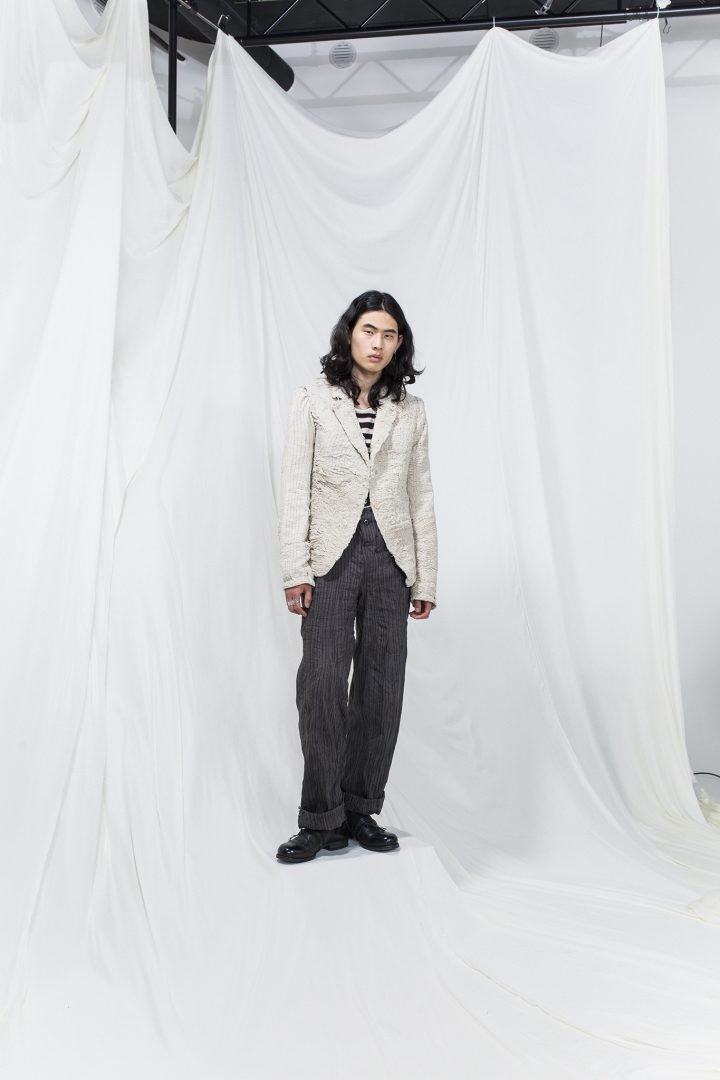 Model is wearing a striped shirt, grey oversized trousers and white crumpled blazer
