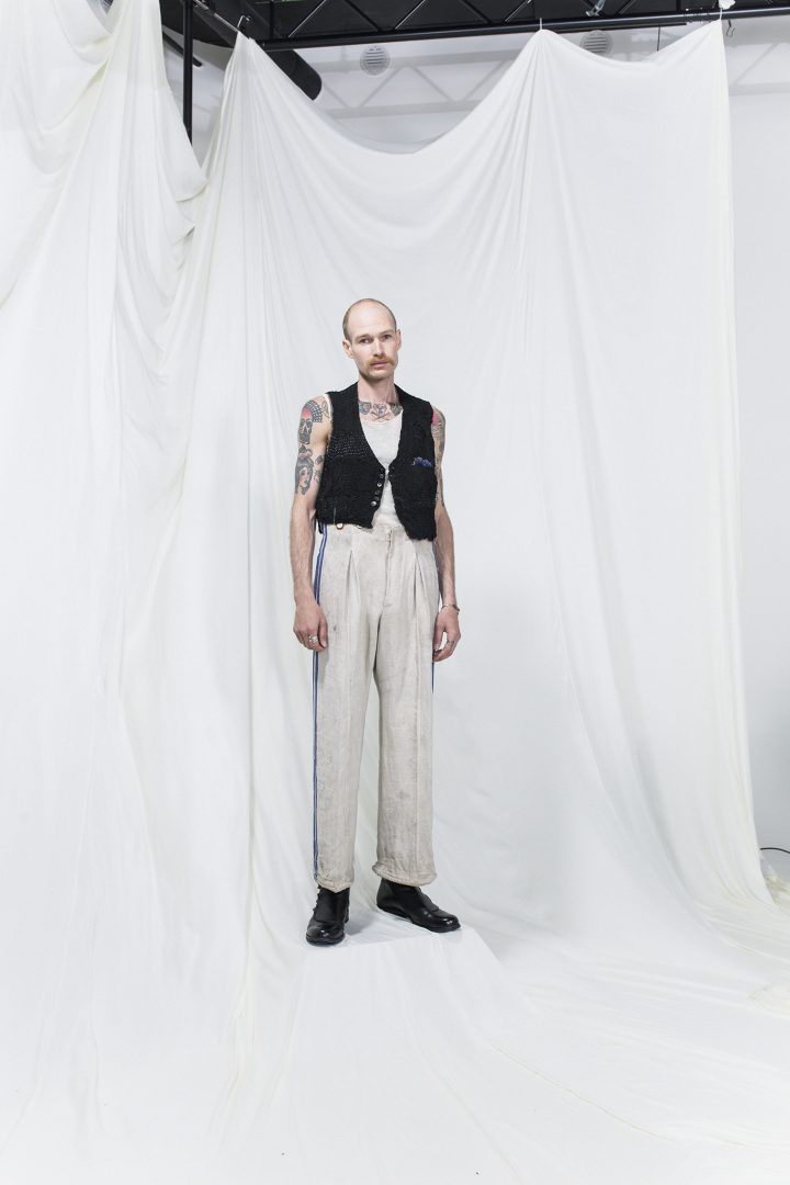 Model is wearing a white tank top, black vest and oversized trousers with blue stripes and suspenders
