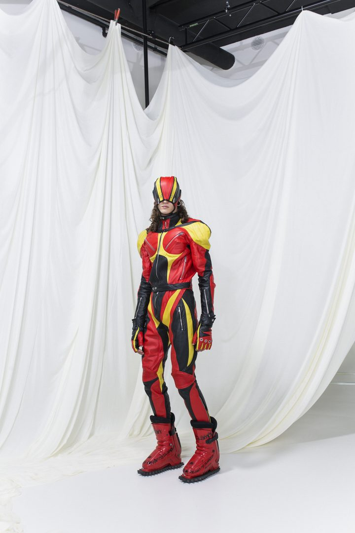 Model is wearing a muscle leather overall in red, yellow and black, with matching gloves and mask. Red boots