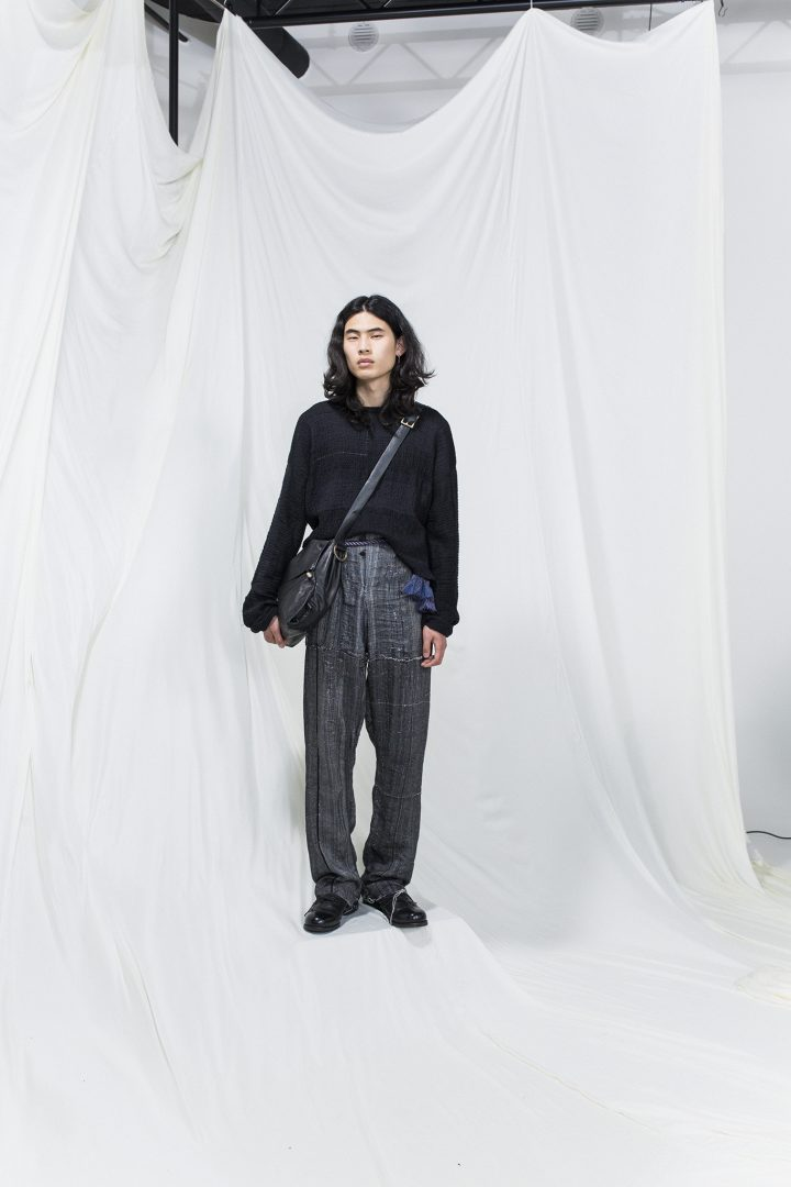 Model is wearing a oversized black sweater, oversized grey trousers and black leather crossbody bag