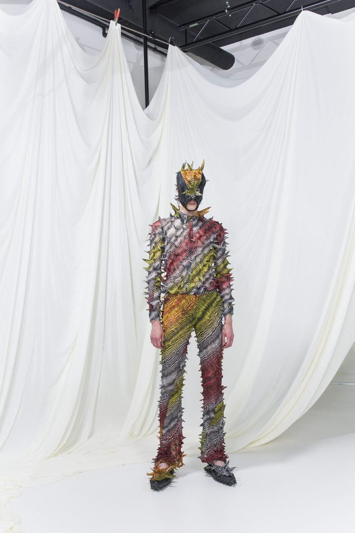 Model is wearing a multicolored striped & spiked shirt and jeans with matching mask