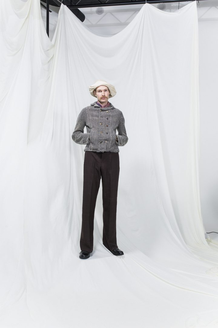 Model is wearing a short grey jacket and brown suit trousers