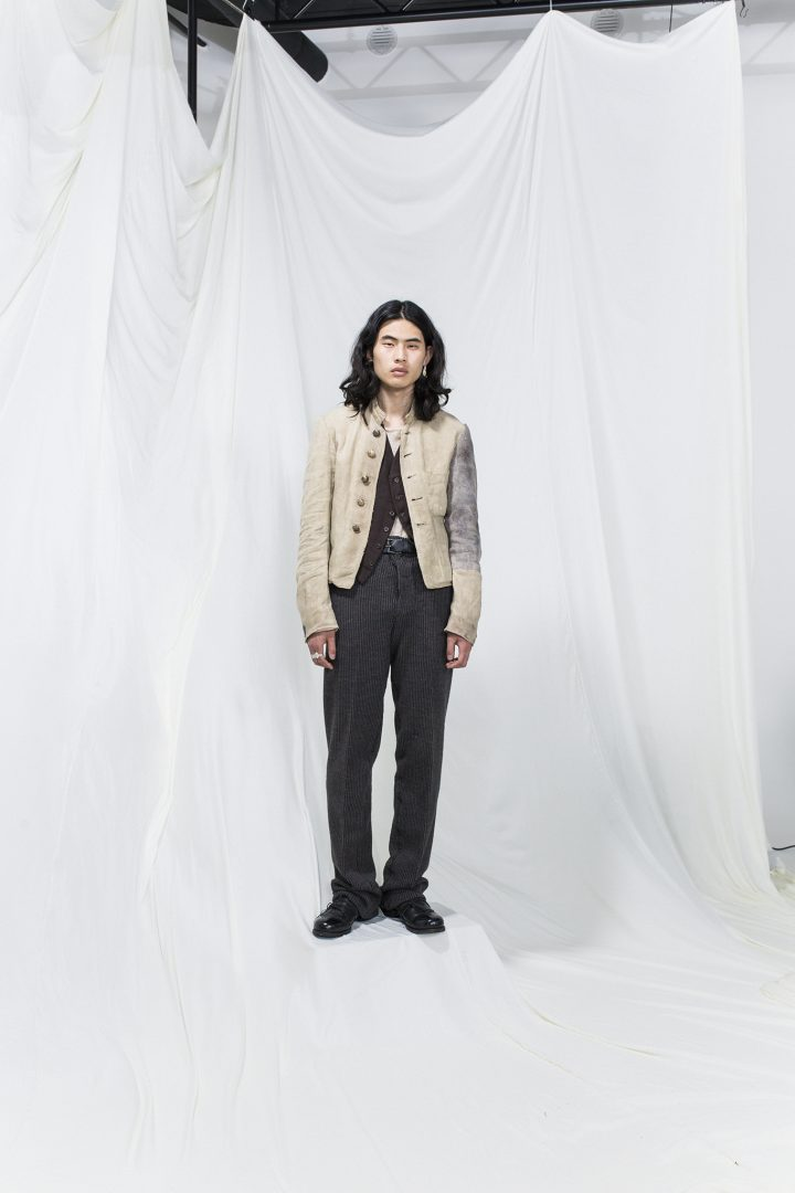 Model is wearing a dark brown vest and grey trousers, white jacket with one arm grey from the shoulder