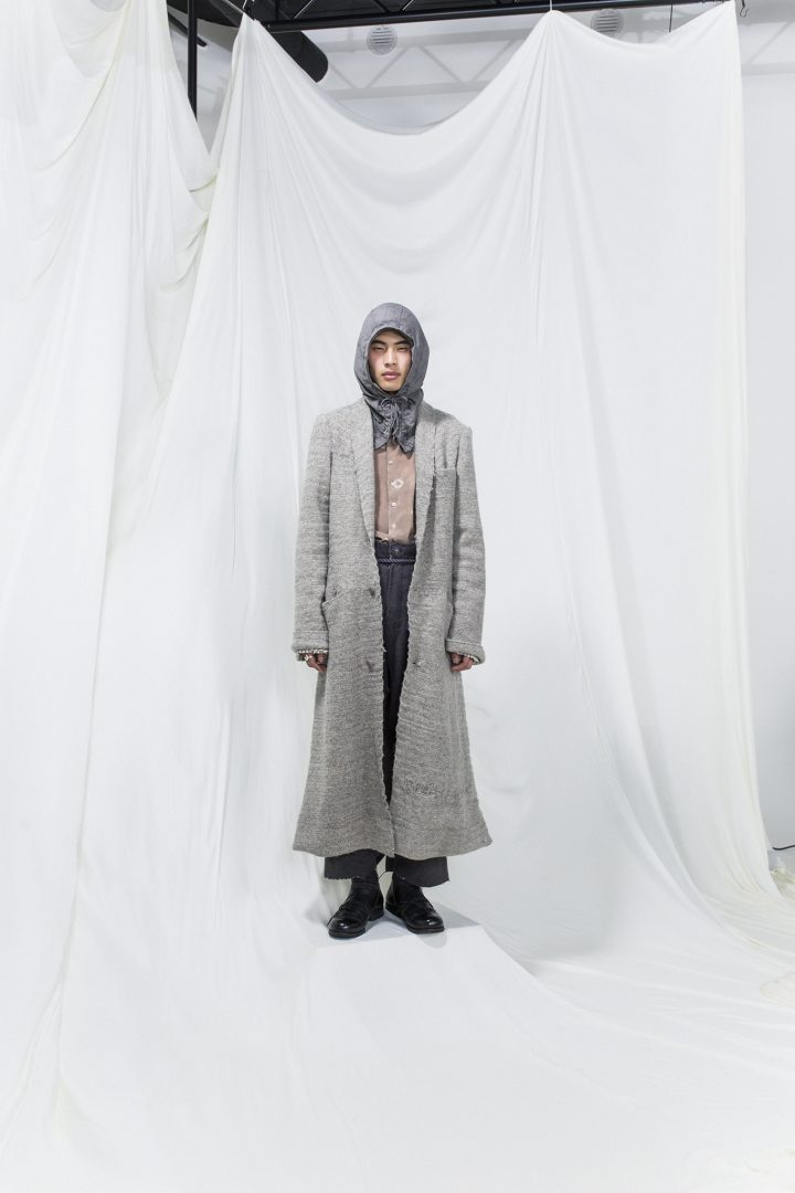 Model is wearing a light grey coat, dark grey hoodie. Underneath pink buttoned shirt and grey oversized trousers