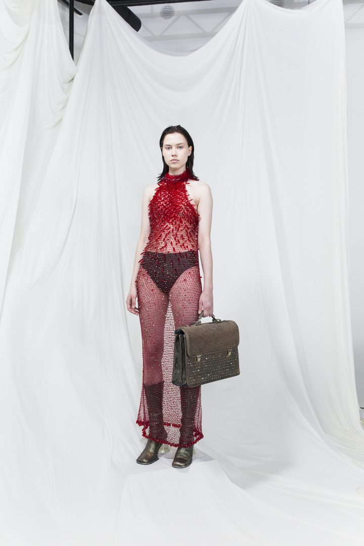 Model is wearing a red sheer long dress with long red plastic crystals. Olive green suitcase and same-coloured heels as accessories