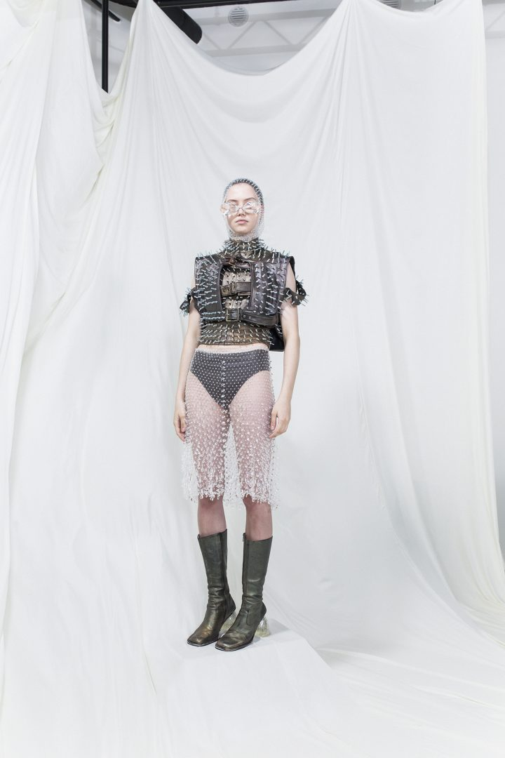 Model is wearing a spiked brown and green leather vest with buckles, sheer sequinned skirt and scarf