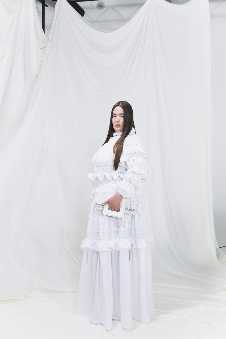 Model is wearing a white modular gown with puffy sleeves and matching white clutch