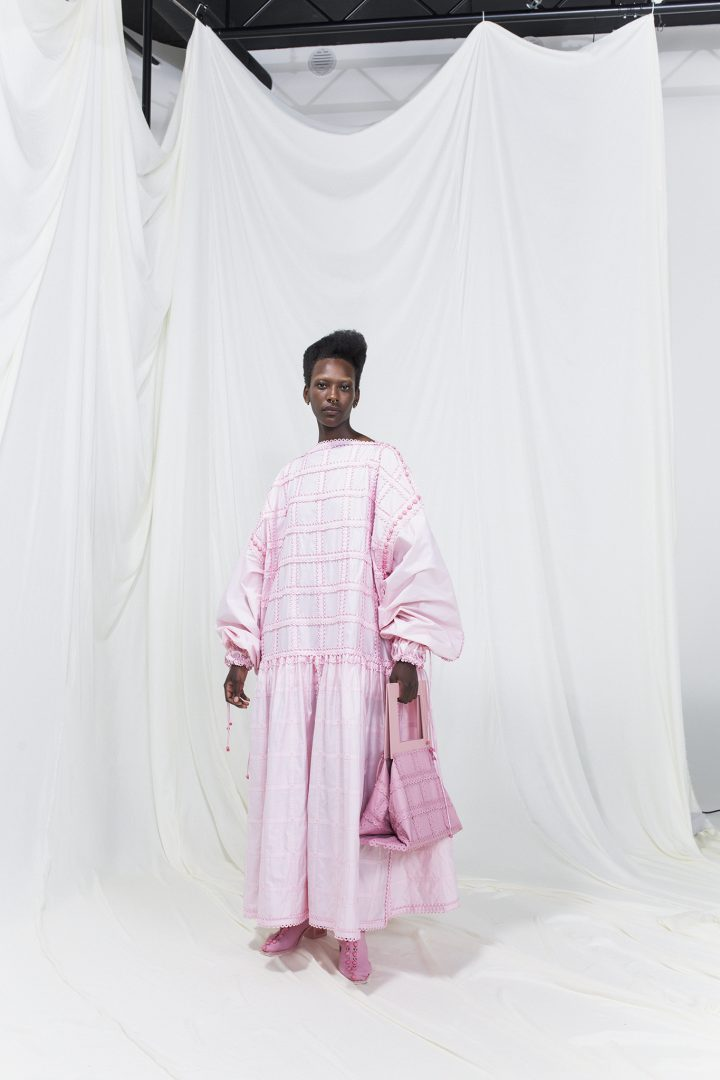 Model is wearing a pale pink dress with matching handbag and heels
