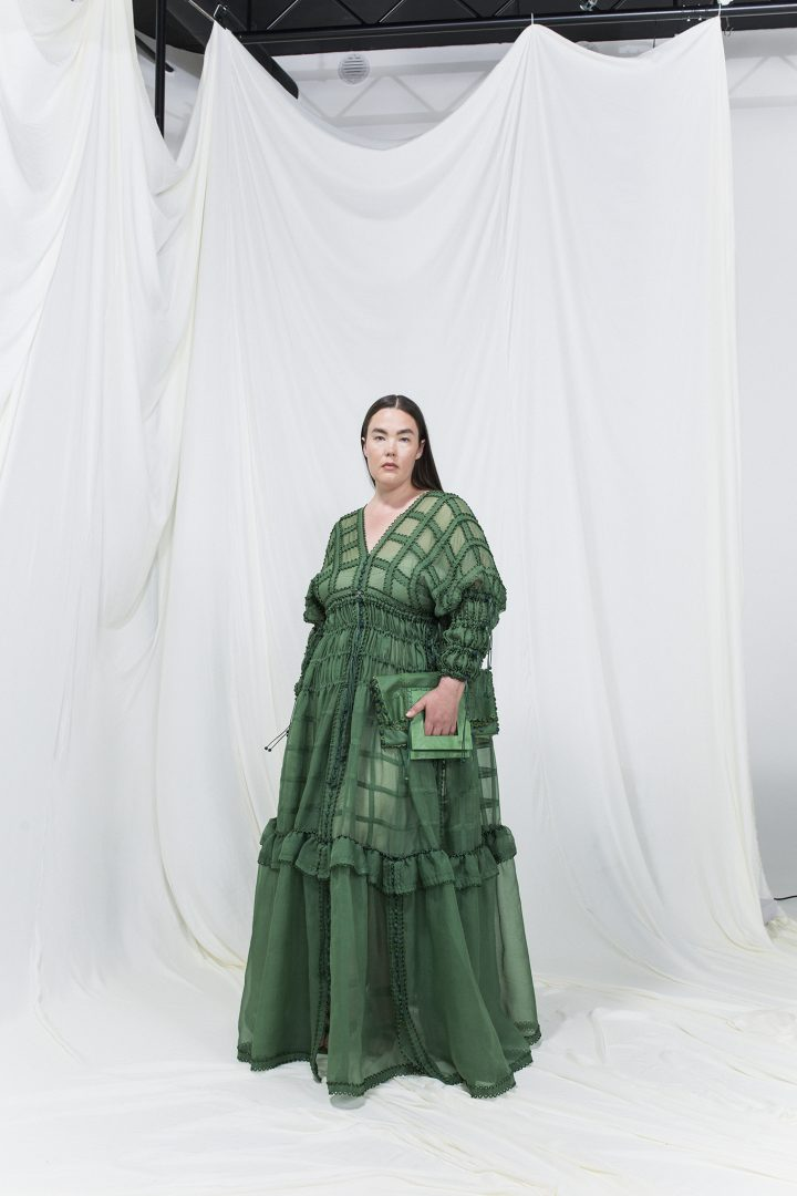 Model is wearing a green modular silk organza gown with matching green leather clutch