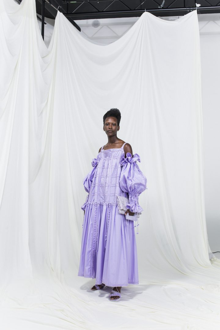 Model is wearing a lilac modular silk dress with oversized sleeves and matching violet heels